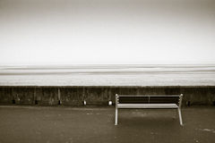 Bench in front of the ocean. In black and white royalty free stock photography