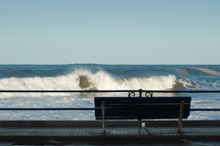 Bench in front of the sea, with big waves Stock Image