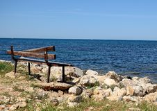 Bench in front of the sea stock photography