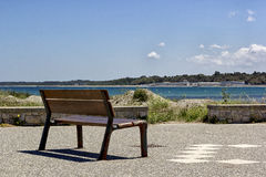 Bench in front of the sea Stock Images