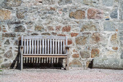 Bench in front of stone wall Stock Image
