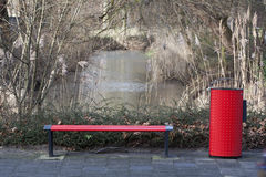 Bench and garbage can. Red metal bench and wastepaper basket Stock Photography