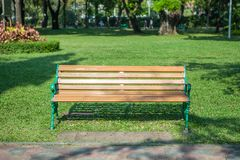 Bench in the garden park on green grass.  Stock Image