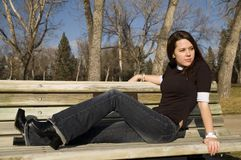 Bench girl. Girl sitting on a park bench in the fall time Stock Image