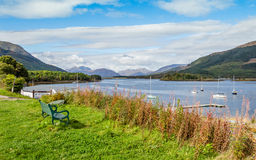 Bench at Glecoe, Scotland. GLENCOE, HIGHLAND, SCOTLAND - SEPTEMBER 24, 2014: lone bench with a relaxing view of Loch Leven and Coe river valley in a sunny Royalty Free Stock Photos