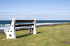 Bench on grass next to the ocean Royalty Free Stock Image