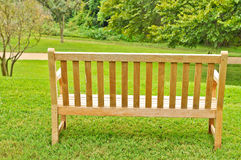 Bench on grass by a tree Stock Photo