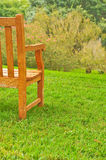 Bench on grass by a tree Stock Images