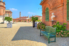 Bench on gravel next to brick house in Piedmont, Italy. Stock Images