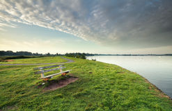 Bench on green grass by big lake Stock Photo