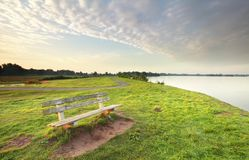 Bench on green grass by lake Stock Image