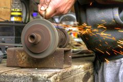 Bench grinder. Metal grinding on home-made bench grinder generating sparks stock photography