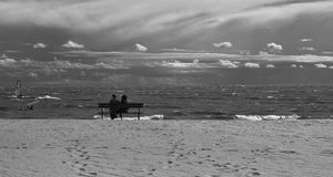 Bench on the Gulf of Finland. Woman and man sitting on a bench on the Gulf of Finland Stock Image