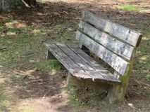 A weary old bench provides a resting place by a serene waterway. This bench has aged over time and weather, but sits by the side of a beautiful waterway. A stock photo