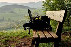 Bench on the hill. Backpack on a wooden bench with highland on background stock photos