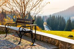 Bench on a hill in beautiful autumn countryside. Lovely mountainous landscape with road through forest Royalty Free Stock Image