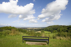 Bench on hill overlooking scenic view of countryside Stock Photography