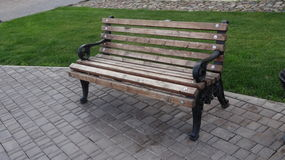 Bench in a holiday park on the pavement next to litter bin. Wooden bench, with metal legs in the park on the sidewalk next to the urn Stock Photography