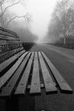 Bench im Park an einem nebeligen und regnerischen Tag Lizenzfreies Stockfoto