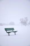 Bench im schneebedeckten Park Stockfotos
