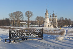 Bench with the inscription `Let`s sit, pookaem` on the embankment rivers Vologda and view of the Church Candlemas of the Lord Stock Photo