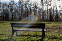 Bench in park and rainbow royalty free stock photo