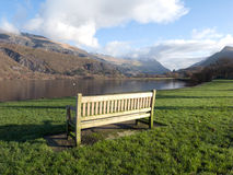 Bench by lake. A wooden bench on green grass next to lake Padarn with a view of mountains in the Snowdonia national park, Wales, UK Royalty Free Stock Photos