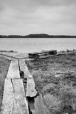 Bench by the lake. A black and white photo of resting place with timber bench by the lake in a swamp Stock Images