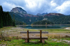 Bench on lake. Empty wooden bench with view on mountain, glacial lake in autumn and dramatic, cloudy sky Stock Photo