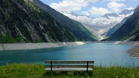 Bench and lake and mountains and glaciers and snow and clouds and grasses and sunny summer day in the Alps Royalty Free Stock Image