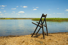Bench by the lake. Old wooden chair on beautiful river bank Royalty Free Stock Photography
