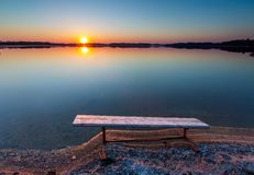 Bench on lake shore at sunset Royalty Free Stock Images