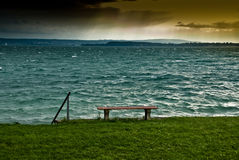 Bench on lake shoreline Royalty Free Stock Photography