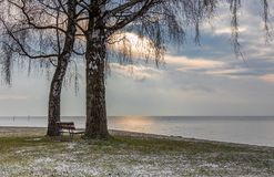 Bench. Lake. Water. Leman. Sunrise. Color. Sky. Beautiful winter sunrise on the lake Leman, near the Lausanne city. Wooden bench on the park. Winter and snow stock images