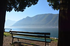 Bench by the lake. A wooden bench standing in the sunshine by the lake, surrounded by hills Royalty Free Stock Photo
