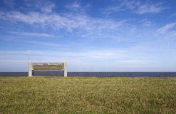 Bench on lakeshore under blue sky Stock Photo