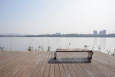 Bench on lakeside planked platform in sunny winter afternoon. A bench on lakeside planked platform in sunny winter afternoon,Chengdu,China stock photo