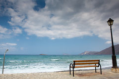 A bench and lantern at sea. A bench, a lantern and a public shower on an empty beach in Crete. The weather will become soon bad wit heavy clouds in the sky Stock Photography