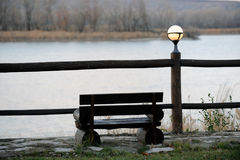 The bench and lanterns are a beautiful place for solitude over the river. At sunset royalty free stock image