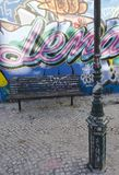 A bench and a light pole in Calcado do Lavra street in Lisbon Royalty Free Stock Photography