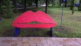Bench for lips-shaped kisses in a city park. Red lips royalty free stock images
