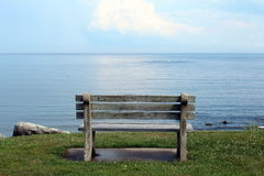 Bench looking out to sea. Cement and wood bench on a cliff overlooking a calm sea Royalty Free Stock Image