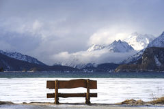 Bench looking solitary at frozen Sils lake in Engadin Switzerland with snow Alps mountains Royalty Free Stock Image