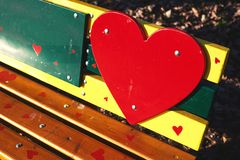 Bench of Love. Colorful park bench decorated with wooden parts painted in vivid colors in shape of heart Stock Image