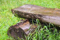 Bench made of logs in the meadow green grass Royalty Free Stock Photo