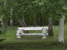 Bench made of wooden logs, similar to birch, standing in a fores Royalty Free Stock Photos