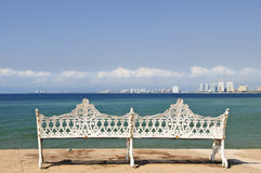 Bench on Malecon in Puerto Vallarta, Mexico. White metal bench on Malecon at Pacific ocean in Puerto Vallarta, Mexico Stock Photo