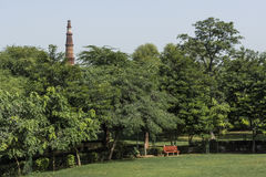 Bench in Mehrauli archaeological park and Qutub Minar seen in background. Stock Photography