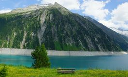 Bench and mountain lake and glaciers and clouds and grasses and yellow flowers and fresh water in the Alps for relaxation Royalty Free Stock Image