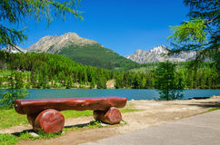 Bench, mountain lake and peaks of High Tatras Royalty Free Stock Image